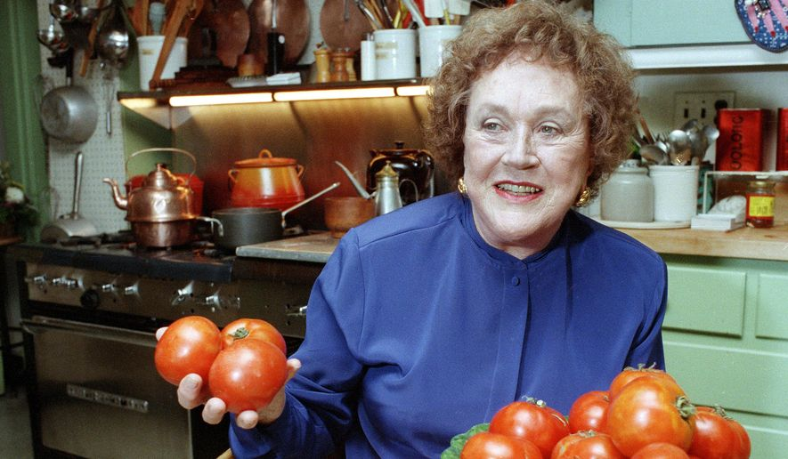 FILE - In this Aug. 13, 1992 file photo, chef and author Julia Child holds tomatoes in the kitchen at her home in Cambridge, Mass. More than a decade after her death, the foundation she created finally is launching a culinary award named in her honor. The Julia Child Award, which will be named annually, will be presented to someone who has improved how Americans think about food and cooking. The first winner will be announced in August 2015 and the award will be presented in October. (AP Photo/Jon Chase)