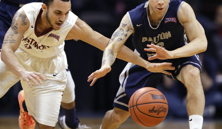Westmont guard Britton Williams, left, reaches for the ball in front of Dalton State guard Sean Tate during the first half of the NAIA championship basketball game in Kansas City, Mo., Tuesday, March 24, 2015. (AP Photo/Orlin Wagner)