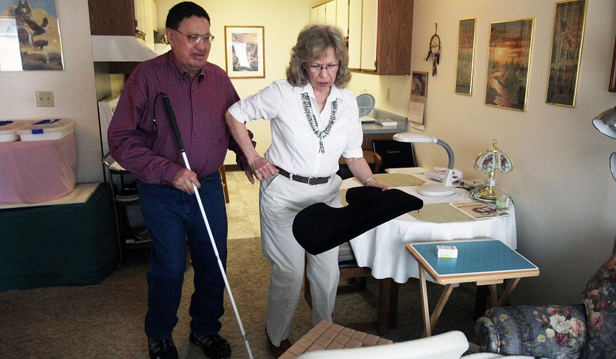 """In this photo taken Aug. 16, 2012, Vern Traversie gets help from his friend, Karen Townsend, navigating through his apartment in Eagle Butte, S.D. A civil trial is underway in a case in which Traversie alleges Rapid City Regional Hospital workers intentionally carved the letters """"KKK"""" into his abdomen during heart surgery.  The Seventy-one-year-old is suing in federal court for alleged violations of civil rights, battery and intentional infliction of emotional distress. He's seeking unspecified money damages. Hospital attorney Jeffrey Hurd says the marks on Traversie's abdomen were the result of a skin reaction to medical tape. (AP Photo/Rapid City Journal) TV OUT"""