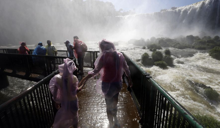 In this March 15, 2015 photo, tourists wear plastic ponchos as they try to stay dry in the spray of Iguazu Falls in Brazil. From above, the Iguazu Falls resemble a massive hole in a river surrounded by thick jungle. Spray from the falls douses the nearby viewing areas where some tourists don rain ponchos while others take off their shirts and dance and hug in the drenching mist. (AP Photo/Jorge Saenz)