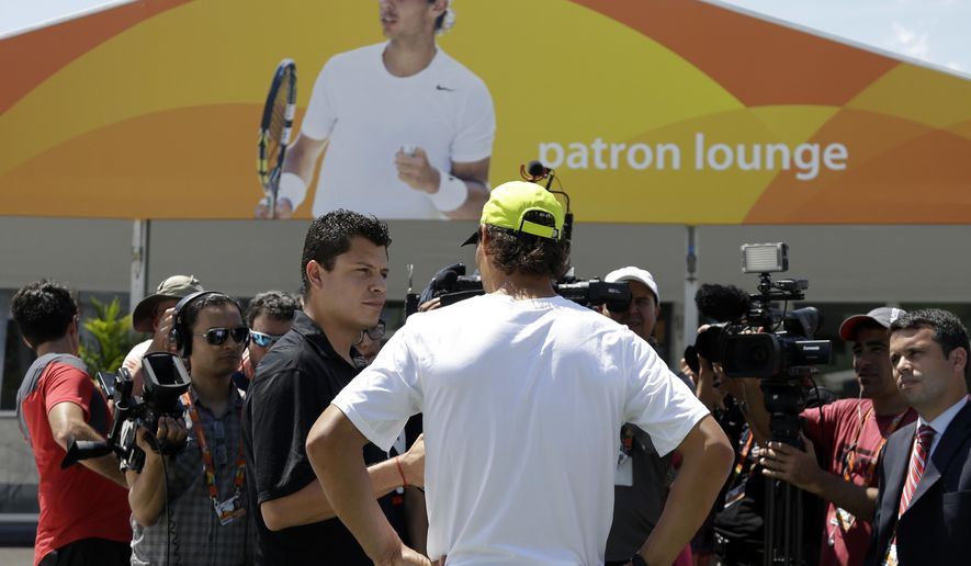 Rafael Nadal, of Spain, center, is interviewed by the news media as an image of him is displayed on a tent at the Miami Open tennis tournament, Tuesday, March 24, 2015, in Key Biscayne, Fla. Nadal plays his first match Friday. (AP Photo/Lynne Sladky)