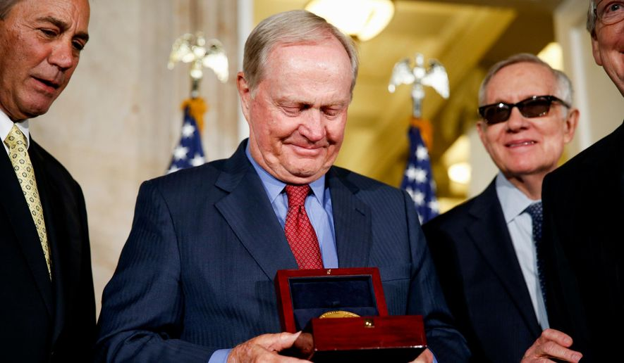 Retired professional golfer Jack Nicklaus looks at a Congressional Gold Medal which was presented to him during a ceremony on Capitol Hill in Washington, Tuesday, March 24, 2015. From left are, House Speaker John Boehner of Ohio, Nicklaus, Senate Minority Leader Harry Reid of Nev., and Senate Majority Leader Mitch McConnell of Ky.  (AP Photo/Andrew Harnik)