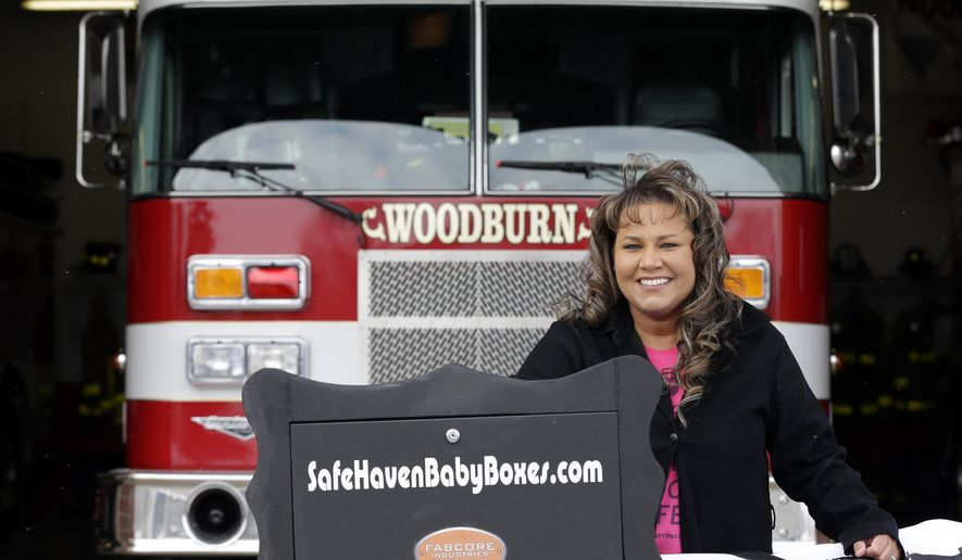 "FILE -  In this Feb. 26, 2015 file photo Monica Kelsey, a firefighter and medic who is president of Safe Haven Baby Boxes Inc., poses with a prototype of a baby box,  where parents could surrender their newborns anonymously, outside her fire station in Woodburn.  An Indiana proposal to allow fire stations and other public places to install ""baby boxes"" so mothers in crisis could anonymously surrender their newborns needs further review and is unlikely to advance this year, a key lawmaker said Tuesday, March 24, 2015. Sen. Patricia Miller, whose Senate health committee is scheduled to hear the bill Wednesday, March 25, said she expects the bill to be amended to send it to study committees for further evaluation.(AP Photo/Michael Conroy, File)"
