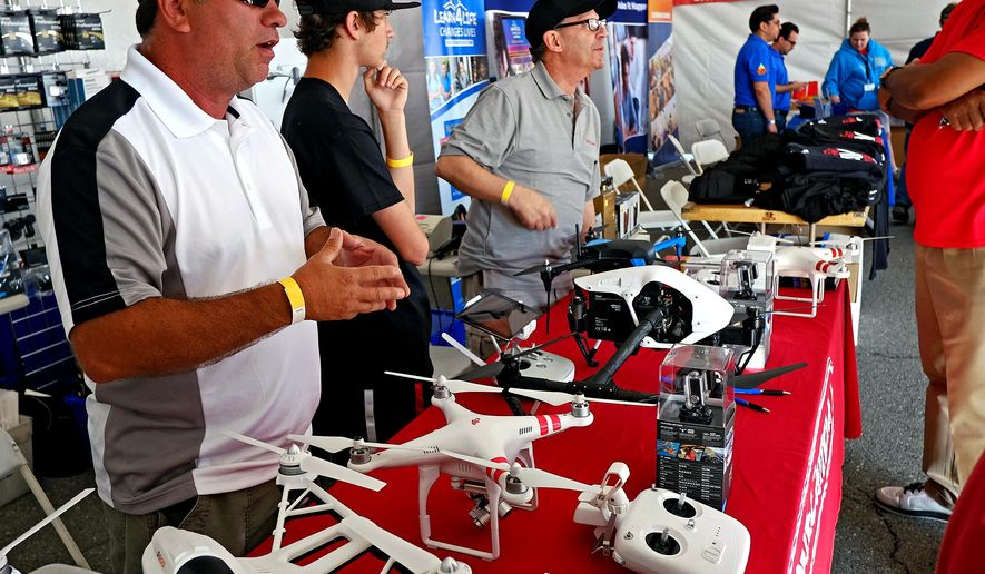 In this Saturday, March 21, 2015 photo, vendors display an assortment of drones at the Los Angeles County Air show at the William J.Fox Airfield in Lancaster, Calif. A Nevada Assemblyman's bill, heard Tuesday, March 24, to implement privacy regulations on drones is expected to meet some opposition from the emerging industry. The bill creates a regulatory framework for drones and includes limitations designed to protect the privacy of citizens. (AP Photo/Richard Vogel)