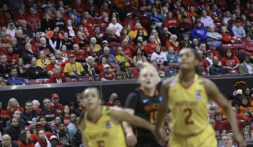 Fans watch as Maryland and Princeton players chase after a rebound in the first half of an NCAA college basketball game in the second round of the NCAA tournament, Monday, March 23, 2015, in College Park, Md. Buoyed by a move back to host sites and more weekend games, overall attendance rose at the women's NCAA Tournament in the opening two rounds. (AP Photo/Patrick Semansky)