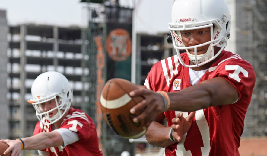 Tennessee quarterbacks Joshua Dobbs (11) and Devin Smith (17), from right, run drills during Tennessee's opening spring football practice at Haslam Field on Tuesday, March 24, 2015 in Knoxville, Tenn. (AP Photo/Knoxville News Sentinel, Adam Lau)