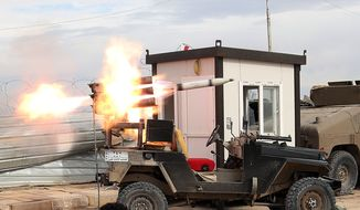 Members of an Iraqi Shiite militant group called Imam Ali Brigades launch rockets against Islamic State extremist positions during clashes in Tikrit, 130 kilometers (80 miles) north of Baghdad, Iraq, Tuesday, March 24, 2015. (AP Photo/Khalid Mohammed)