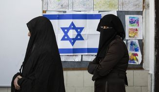 FILE - In this Tuesday, March 17, 2015 file photo, Bedouin women wait to cast their votes at a polling station in the town of Rahat, Israel on for parliament elections. After a strong performance in last week's parliamentary election, Prime Minister Benjamin Netanyahu seems to be cruising toward forming a new government of hardline and religious parties. But in the smoke-and-mirrors world of Israeli politics, a centrist government more amenable to peace negotiations could easily emerge at the last minute instead. (AP Photo/Tsafrir Abayov, File)