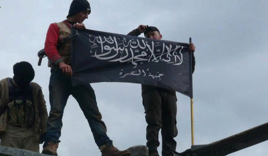 Rebels from al Qaeda-affiliated Jabhat al-Nusra, also known as the Nusra Front, wave their brigade flag as they step on the top of a Syrian air force helicopter at Taftanaz air base on Jan. 11, 2013. (Associated Press) **FILE**