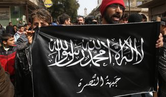 FILE- In this  Friday, March 1, 2013 file photo, anti-Syrian President Bashar Assad protesters hold the Jabhat al-Nusra flag, as they shout slogans during a demonstration, at Kafranbel town, in Idlib province, northern Syria. The Nusra Front, Syria's al-Qaida affiliate, is consolidating power in territory stretching from the Turkish border to central and southern Syria, crushing moderate opponents and forcibly converting minorities using tactics akin to its ultraconservative rival, the Islamic State group. (AP Photo/Hussein Malla, File)