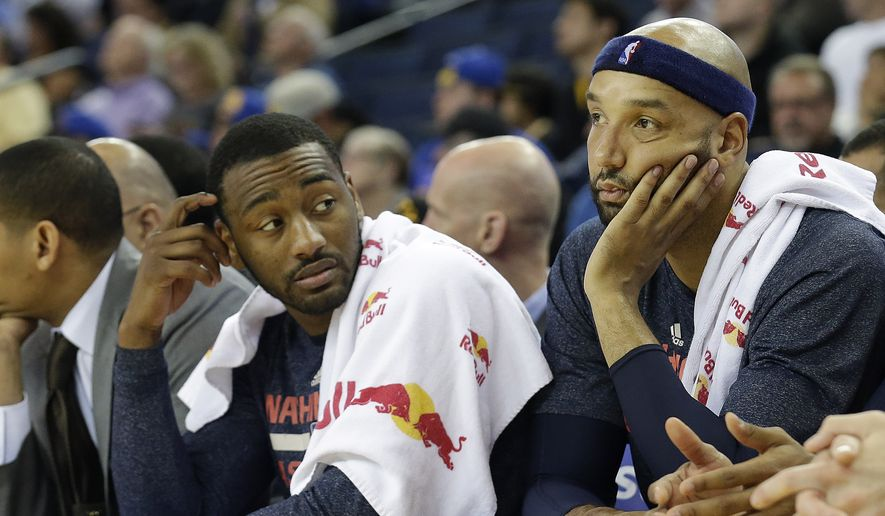 Washington Wizards guard John Wall, left, and forward Drew Gooden sit on the bench during the second half of an NBA basketball game against the Golden State Warriors in Oakland, Calif., Monday, March 23, 2015. The Warriors won 107-76. (AP Photo/Jeff Chiu)