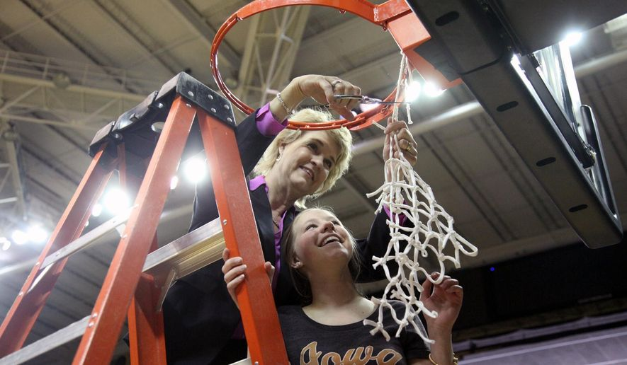 Iowa head coach Lisa Bluder. top, cuts down the net with help from her daughter Emma Bluder after defeating Miami in a women's college basketball game in the second round of the NCAA tournament in Iowa City, Iowa, Sunday March 22, 2015. (AP Photo/Matthew Holst)