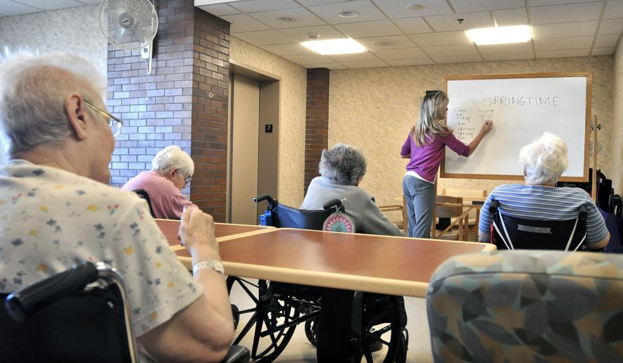 FILE - In this Feb. 28, 2013, file photo, Tina Reese leads a word game for residents at a nursing home in Lancaster, Pa. Life insurance firms pitched long-term care policies as the prudent way for Americans to shoulder the cost of staying in nursing homes. But those same companies have found that long-term-care policies are squeezing their profits. (AP Photo/Intelligencer Journal, Dan Marschka, File)