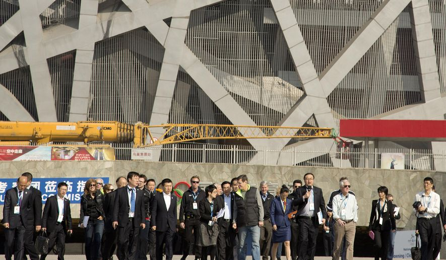 Members of the 2022 Evaluation Commission for the International Olympic Committee (IOC) and representatives of Beijing's 2022 Winter Olympics Bid Committee walk outside Beijing National Stadium, also known as the Birds' Nest, in Beijing, Tuesday, March 24, 2015. (AP Photo/Mark Schiefelbein, Pool)