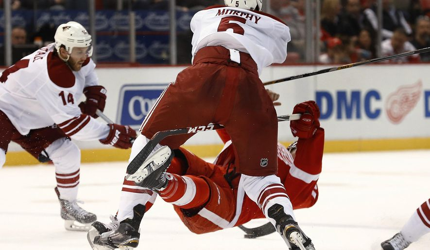 Arizona Coyotes defenseman Connor Murphy (5) checks Detroit Red Wings right wing Luke Glendening during the second period of an NHL hockey game in Detroit on Tuesday, March 24, 2015. (AP Photo/Paul Sancya)