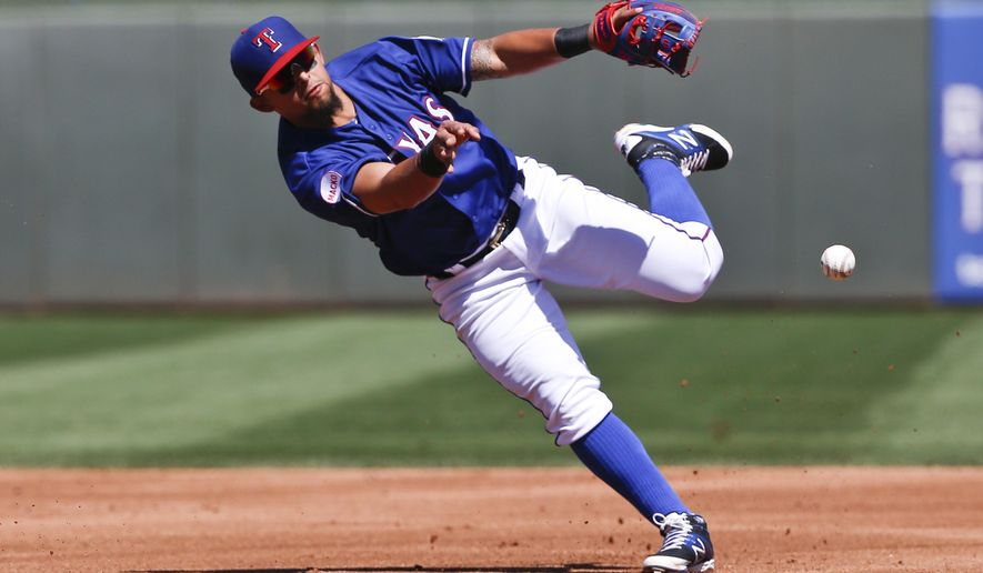 Texas Rangers second baseman Rougned Odor makes an off-balance throw to get the out at first after fielding a slow roller hit by Anaheim Angels' Erick Aybar during the third inning of a spring training baseball game Tuesday, March 24, 2015, in Surprise, Ariz. (AP Photo/Lenny Ignelzi)