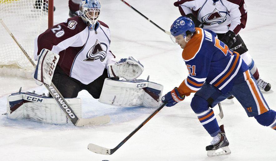 Colorado Avalanche goalie Reto Berra (20) defends Edmonton Oilers' Anton Lander (51) during the second period of an NHL hockey game Wednesday, March 25, 2015, in Edmonton, Alberta. (AP Photo/The Canadian Press, Jason Franson)