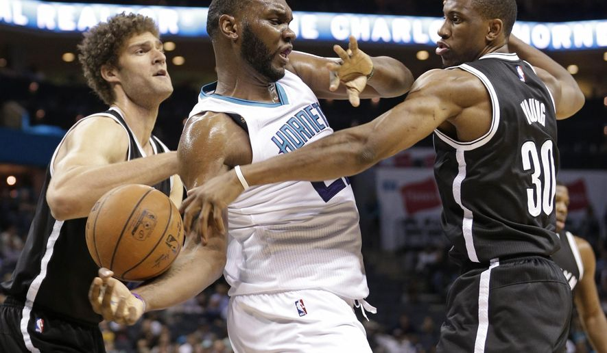 Charlotte Hornets' Al Jefferson, center, loses the ball as he is trapped by Brooklyn Nets' Brook Lopez, left, and Thaddeus Young, right, during the first half of an NBA basketball game in Charlotte, N.C., Wednesday, March 25, 2015. (AP Photo/Chuck Burton)