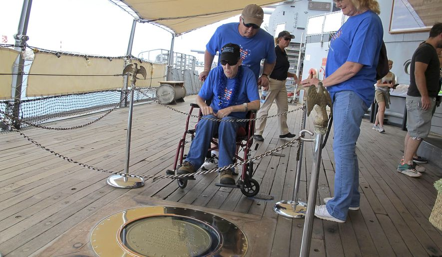Joseph Hooker, a terminally ill Vietnam veteran, sits in a wheelchair and looks at the spot on the battleship USS Missouri where Japan surrendered in 1945 during a tour with his brother Lester Hooker, center standing, and sister-in-law Rennie Hooker in Pearl Harbor, Hawaii, Wednesday, March 25, 2015. Joseph Hooker's longtime dream to visit Pearl Harbor has come true. The Dream Foundation arranged for the 63-year-old to travel from his home in Essex, Maryland, to Hawaii. (AP Photo/Jennifer Sinco Kelleher)