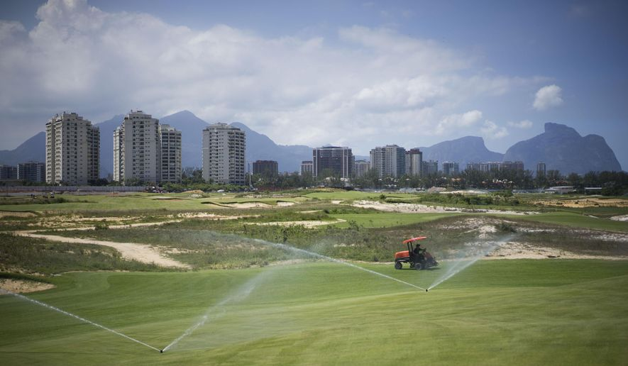 A worker cuts the grass on the Olympic Golf course in Rio de Janeiro, Brazil, Wednesday, March 25, 2015. The mayor of Rio Eduardo Paes, has defended the city's controversial Olympic golf course, which has become a touchstone of criticism from environmental activists and is at the center of complicated legal wranglings since the course was partially carved out of a nature reserve. (AP Photo/Felipe Dana)