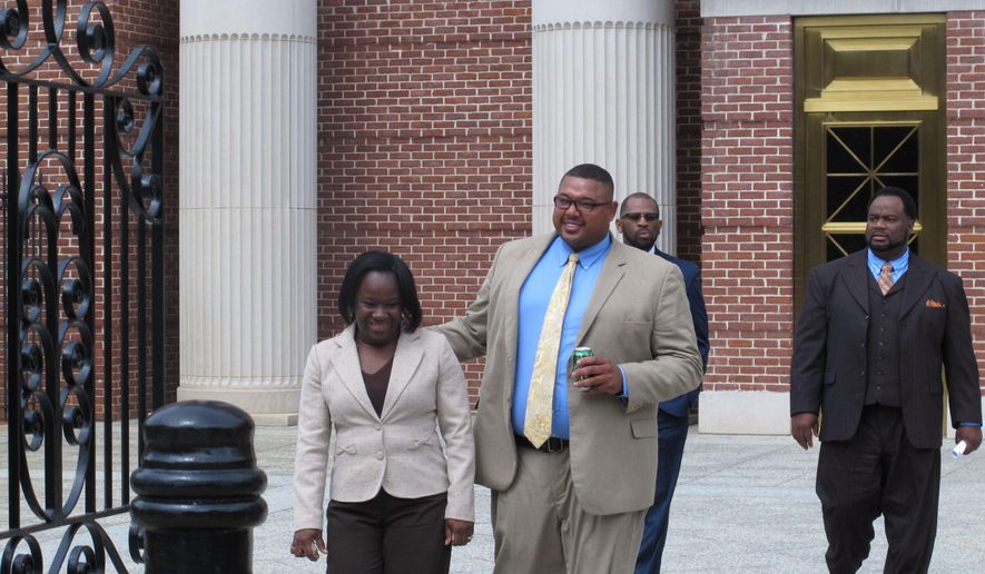 Former Williamsburg County Sheriff Michael Johnson, right, walks out of federal court on Wednesday, March 25, 2015, in Columbia, S.C. Johnson is awaiting his sentence for a mail fraud scheme where prosecutors said he created false police reports to help people improve their credit scores. (AP Photo/Jeffrey Collins)