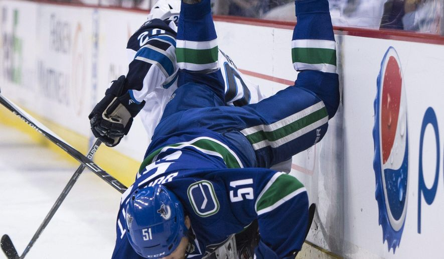 Vancouver Canucks' Derek Dorsett (51) flies over Winnipeg Jets' Lee Stempniak (20) during the first period of an NHL hockey game Tuesday, March 24, 2015, in Vancouver, British Columbia. (AP Photo/The Canadian Press, Jonathan Hayward)