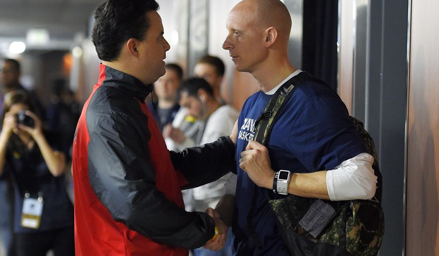 Arizona head coach Sean Miller, left, talks with Xavier head coach Chris Mack between practices at the NCAA college basketball tournament, Wednesday, March 25, 2015, in Los Angeles. Arizona plays Xavier in a regional semifinal on Thursday. (AP Photo/Mark J. Terrill)