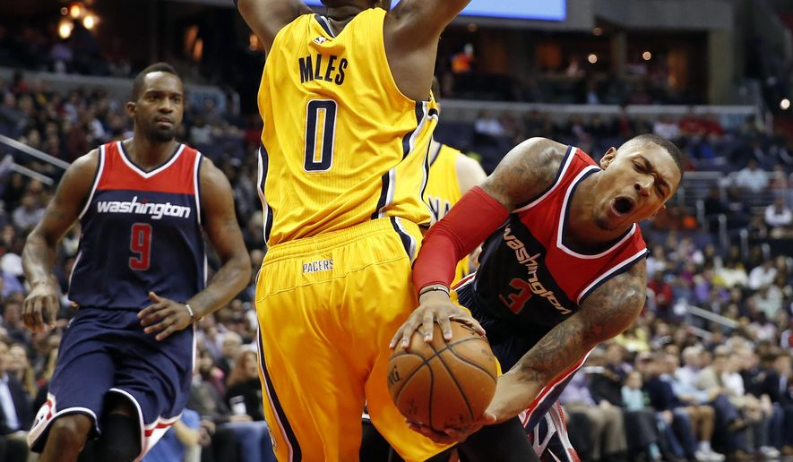 Washington Wizards guard Bradley Beal (3) collides with Indiana Pacers guard C.J. Miles (0) during the first half of an NBA basketball game Wednesday, March 25, 2015, in Washington. Beal left the game with a right ankle sprain. (AP Photo/Alex Brandon)