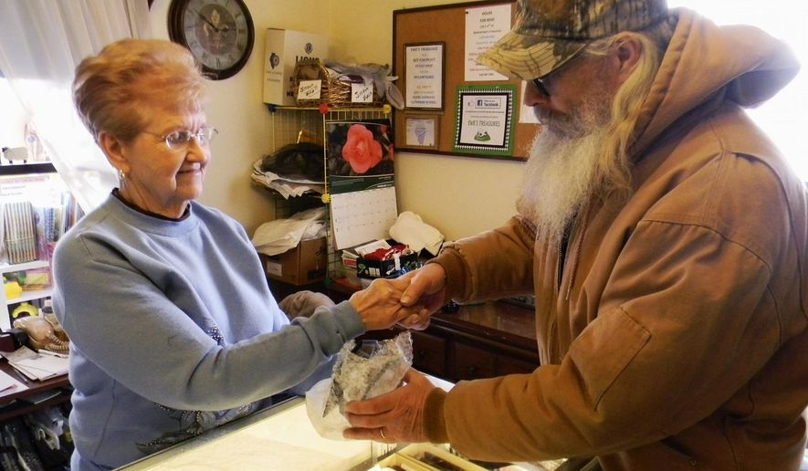 In this Feb. 24, 2015 photo, Eddy Davis, right, of Pekin, Ill., makes a purchase at the Ewe's Treasures Shop in Pekin with volunteer Betty Weyhrich a week after the store hit the milestone of selling $1 million of merchandise. The store, which operates with volunteers only, has been in business for 28 years. (AP Photo/The Pekin Times, Julie Schimmelpfennig)