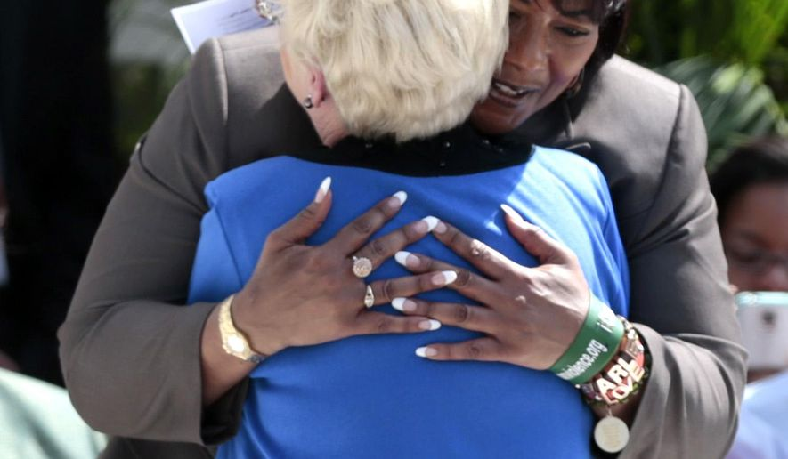 Bernice King hugs Peggy Wallace Kennedy after her speech to a crowd of people gathered at the steps of the Alabama State Capitol after a march from Selma, Alabama, Wednesday, March 25, 2015, in  Montgomery, Ala.  The daughters of Martin Luther King Jr. and former Alabama Gov. George Wallace, shared a stage on the steps of the Alabama Capitol on Wednesday to mark the 50th anniversary of the 1965 Selma-to-Montgomery voting rights march.  (AP Photo/Butch Dill)