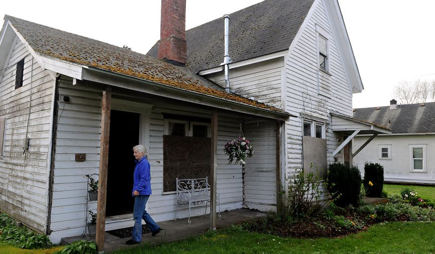 Homeowner Patricia Benner strolls along the outside of the Gorman House, which is the oldest existing residence in Oregon directly tied to early black pioneers, in Corvallis, Ore., on Tuesday, March 17, 2015. (AP Photo/The Gazette-Times, Amanda Cowan)