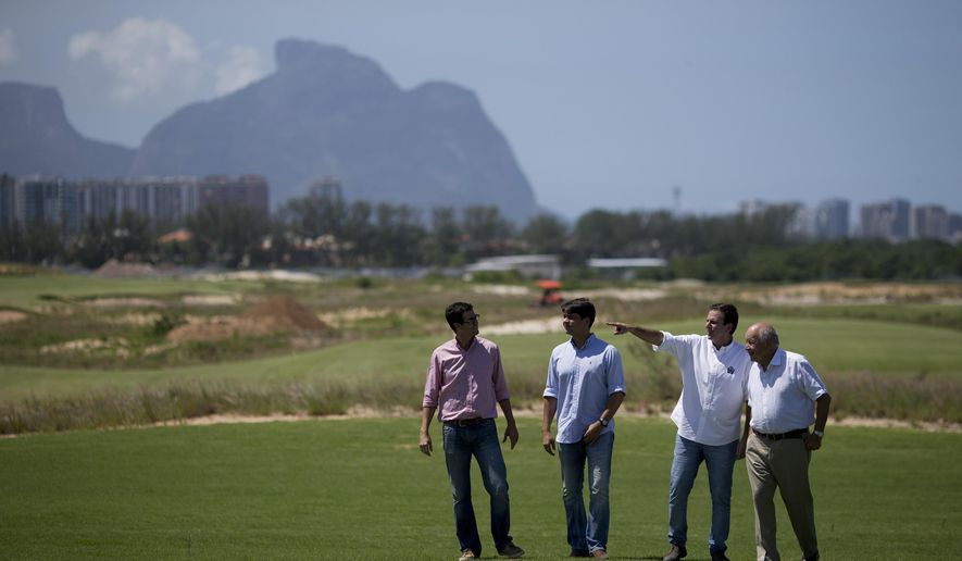 Rio de Janiero's mayor Eduardo Paes, second right, gestures during a visit to the Olympic Golf course in Rio de Janeiro, Brazil, Wednesday, March 25, 2015. The mayor has defended the city's controversial Olympic golf course, which has become a touchstone of criticism from environmental activists and is at the center of complicated legal wranglings since the course was partially carved out of a nature reserve. (AP Photo/Felipe Dana)