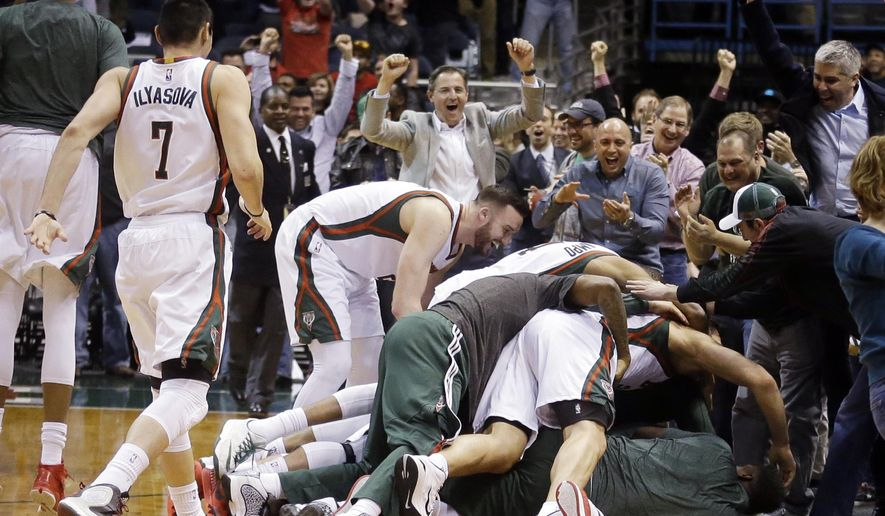 Milwaukee Bucks' Khris Middleton is smothered by teammates after making the game-winning shot in an NBA basketball game against the Miami Heat on Tuesday, March 24, 2015, in Milwaukee. The Bucks won 89-88. (AP Photo/Morry Gash)