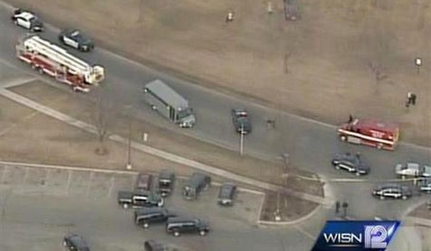 In this frame from video provided by WISN, officials surround the scene following a shooting Tuesday, March 24, 2015, in Fond Du Lac, Wis. Authorities say a Wisconsin state trooper was shot and killed in an exchange of gunfire with a person who matched the description of a bank robbery suspect. Police said the suspect also was killed. (AP Photo/WISN)