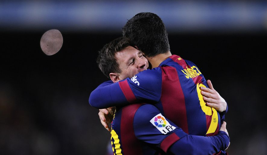 Barcelona's Lionel Messi, left, hugs Luis Suarez after Suarez scored his team's second goal during a Spanish La Liga soccer match between FC Barcelona and Real Madrid at Camp Nou stadium, in Barcelona, Spain, Sunday, March 22, 2015. (AP Photo/Manu Fernandez)