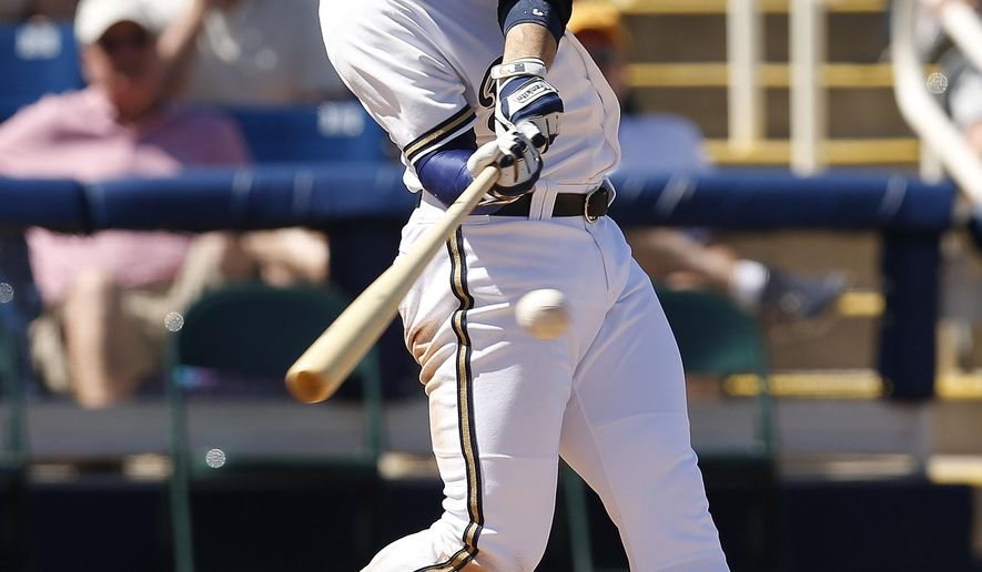 Milwaukee Brewers right fielder Ryan Braun hits an RBI double in the second inning against the Oakland Athletics during a spring training baseball game on Wednesday, March 25, 2015, in Phoenix. (AP Photo/Rick Scuteri)