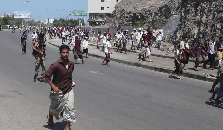 People flee after a gunfire on a street in the southern port city of Aden, Yemen, Wednesday,  March 25, 2015. Yemeni President Abed Rabbo Mansour Hadi fled the country by sea Wednesday on a boat from Aden, as Shiite rebels and their allies advanced on the city where he had taken refuge. Aden was tense Wednesday, with schools, government offices, shops and restaurants largely closed. (AP Photo/Yassir Hassan)