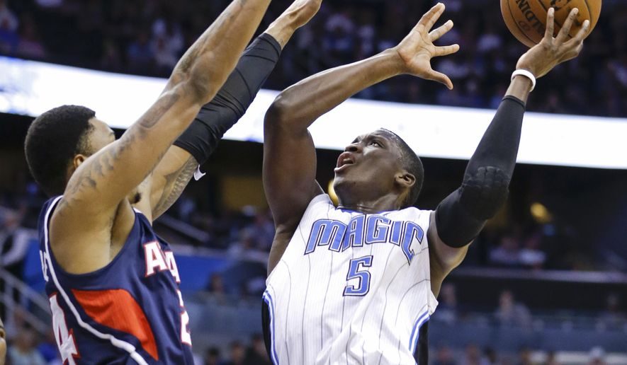 Orlando Magic's Victor Oladipo (5) gets off a shot over Atlanta Hawks' Kent Bazemore, left, during the first half of an NBA basketball game, Wednesday, March 25, 2015, in Orlando, Fla. (AP Photo/John Raoux)