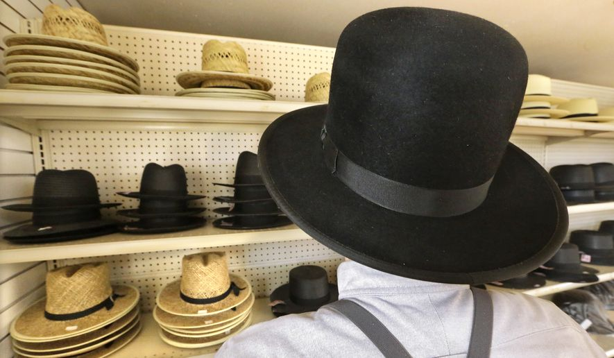 An Amish man shows off a variety of hats he sells in his store in Arthur, Ill. The outcry over a Wisconsin Amish family ordered by a court to leave their home is fueling a legislative push for a religious exemption from building codes requiring smoke alarms and other modern devices. (Associated Press)