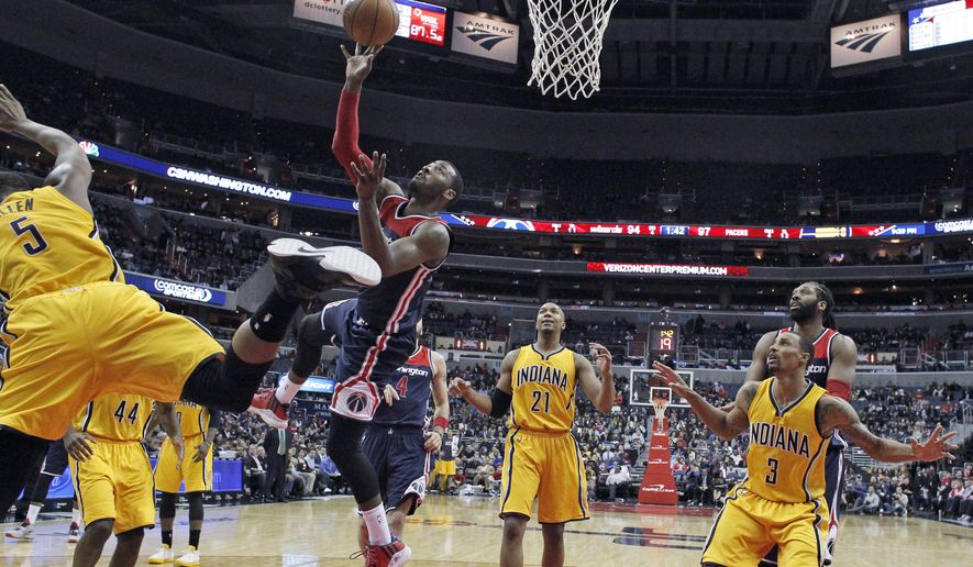 Washington Wizards guard John Wall shoots as Indiana Pacers forward Lavoy Allen (5) jumps past, during the second half of an NBA basketball game Wednesday, March 25, 2015, in Washington. The Pacers won 103-101. (AP Photo/Alex Brandon)