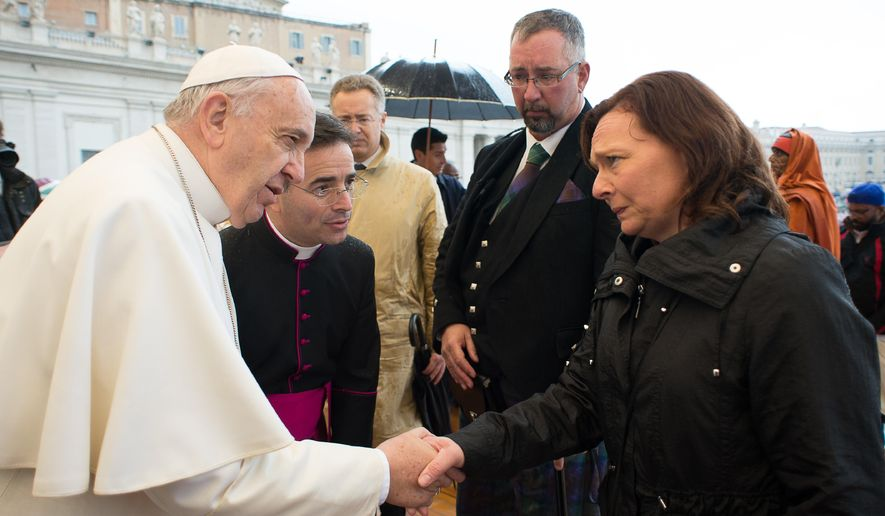 Pope Francis greets Barbara Henning, right, as Michael Haines, second from right, looks at them, during the pontiff's weekly general audience in St. Peter's Square at the Vatican, Wednesday, March 25, 2015. Relatives of two British hostages killed by the Islamic State group have met with Pope Francis as part of efforts to unite people of different faiths to oppose religious extremism. Michael Haines, whose brother David was killed in September, 2014, and Barbara Henning, whose husband Alan was killed the following month, were brought up to greet Francis on the steps of St. Peter's Basilica after his rain-soaked general audience Wednesday. (AP Photo/L'Osservatore Romano, Pool)
