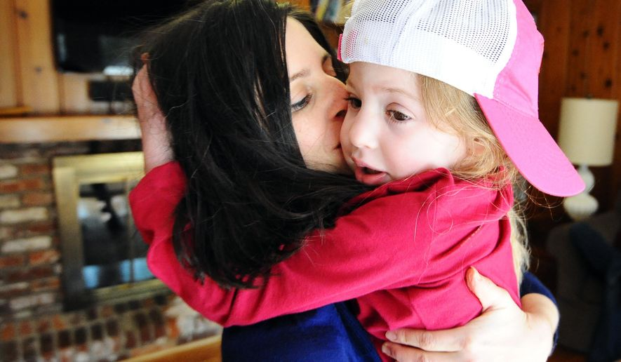 "In this Feb. 21, 2015 photo, Cara O'Neill, left, gives a kiss to her daughter, Eliza, 5, at their home in Columbia, S.C. Glenn and Cara O'Neill started the Cure Sanfilippo Foundation in hopes of saving Eliza, who suffers from the rare disease and is beginning to lose her ability to speak. The disease kills brain cells, causing hyperactivity and autistic-like behavior, then seizures, loss of ability to walk and usually death by the mid-teens. ""The next six or seven years will be horrible for her, and then she'll die,"" her father said. (AP Photo/Rainier Ehrhardt)"