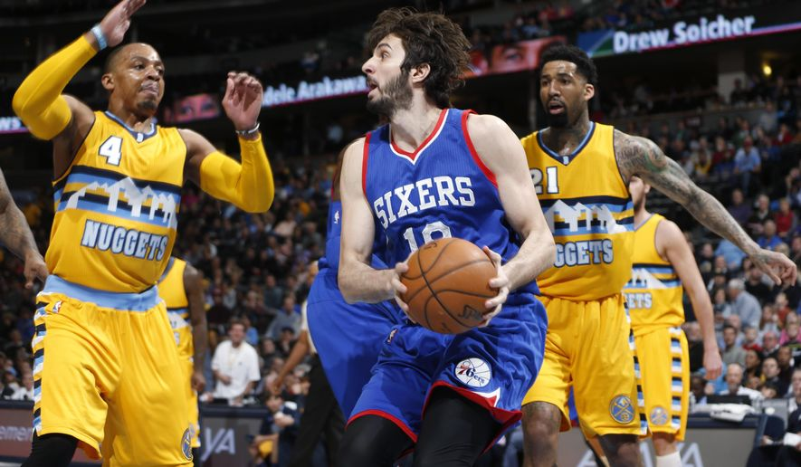 Philadelphia 76ers forward Furkan Aldemir, center, of Turkey, pulls down a rebound between Denver Nuggets guard Randy Foye, left, and forward Wilson Chandler in the first quarter of an NBA basketball game Wednesday, March 25, 2015, in Denver. (AP Photo/David Zalubowski)