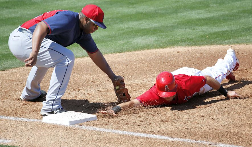Los Angeles Angels' Taylor Featherston slides safely under the pick-off tag of Cleveland Indians' Jesus Aguilar during the second inning of a spring training baseball game, Wednesday, March 25, 2015, Tempe, Ariz.  (AP Photo/Matt York)
