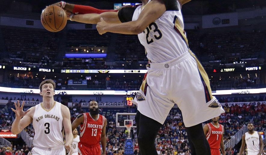 New Orleans Pelicans forward Anthony Davis (23) is blocked by Houston Rockets center Dwight Howard during  the first half of an NBA basketball game in New Orleans, Wednesday, March 25, 2015. (AP Photo/Gerald Herbert)