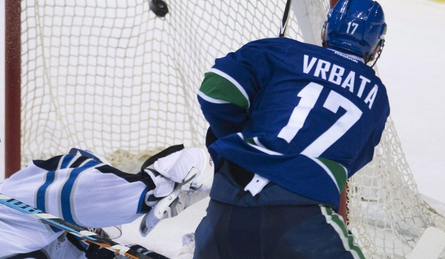 Vancouver Canucks' Radim Vrbata (17) shoots against Winnipeg Jets goalie Michael Hutchinson (34) during the second period of an NHL hockey game Tuesday, March 24, 2015, in Vancouver, British Columbia. (AP Photo/The Canadian Press, Jonathan Hayward)