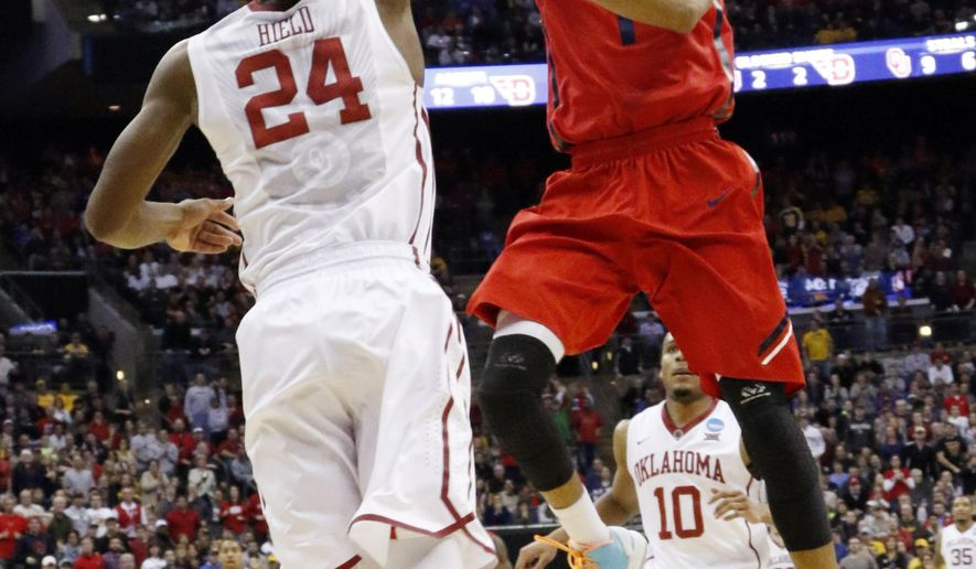 Oklahoma's Buddy Hield (24) blocks a shot by Dayton's Darrell Davis late in the second half of an NCAA tournament college basketball game in the Round of 32 in Columbus, Ohio, Sunday, March 22, 2015. Oklahoma won 72-66 to advance to the Sweet 16. (AP Photo/Paul Vernon)