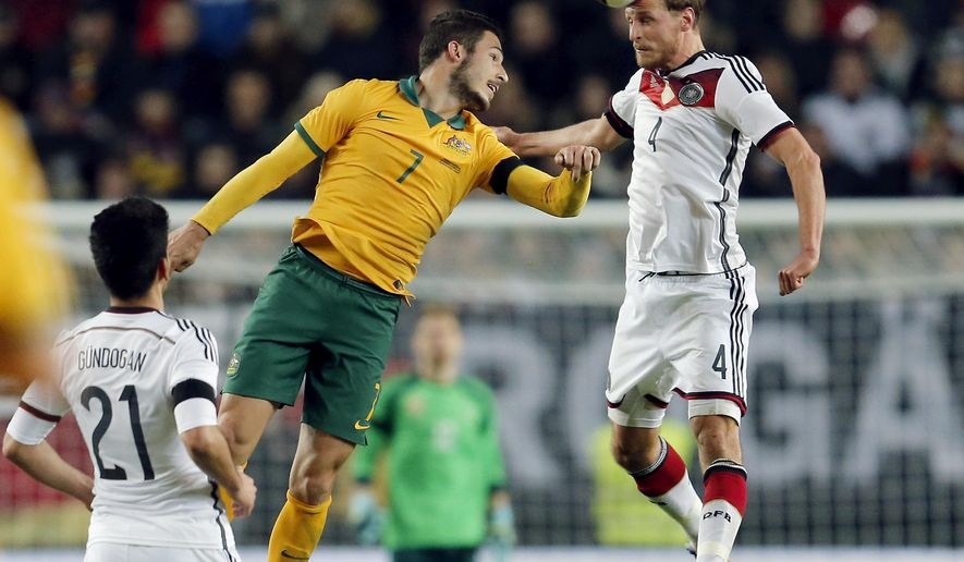 Australia's Mathew Leckie, left, and Germany's Benedikt Hoewedes, right, challenge for the ball during a soccer friendly match between Germany and Australia in Kaiserslautern, Germany, Wednesday, March 25, 2015. (AP Photo/Michael Probst)