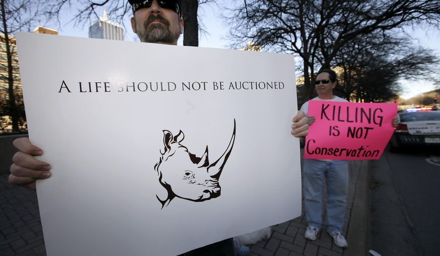 FILE - In this Jan. 11, 2014 file photo, Bob Fretwell of Mesquite, Texas, protests outside the Dallas Convention Center where the Dallas Safari Club is holding a weekend show and auction, where a permit to shoot an endangered black rhinoceros in Africa was up for bid, in Dallas. The U.S. government will allow a Texas man to import the carcass of an endangered black rhinoceros he hopes to kill in Africa as part of a conservation fundraiser. (AP Photo/Tony Gutierrez, File)