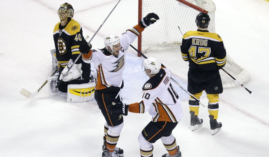 Anaheim Ducks center Ryan Getzlaf, left,  celebrates his winning goal with teammate Corey Perry (10) as Boston Bruins goalie Tuukka Rask (40) and defenseman Torey Krug (47) react in the overtime period of an NHL hockey game in Boston, Thursday, March 26, 2015. The Ducks won 3-2. (AP Photo/Elise Amendola)